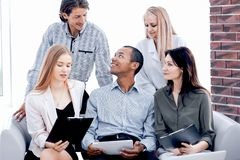 Business woman and her business team discussing the data with a tablet computer stock photo