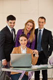 Business woman with her team. Young beautiful business women smiling with a laptop in front of her and three colleagues business people in the back Royalty Free Stock Photos