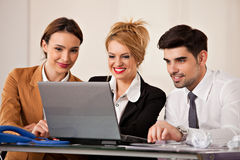 Business woman with her team. Young beautiful business women smiling with a laptop in front of her and two colleagues business people in the back Royalty Free Stock Photos
