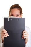 Business woman hiding behind. Young business woman hiding behind a clipboard Stock Image