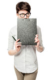 Business woman hiding behind a black folder on a white. Background in studio Stock Photos