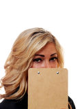 Business woman hiding behind a clipboard. A attractive cute business woman is hiding behind a clipboard Royalty Free Stock Images