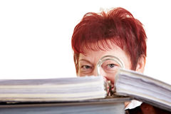Business woman hiding behind files. Elderly business woman hiding behind her files Stock Images