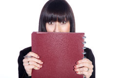 Business woman hiding behind. The ring binder Stock Photo