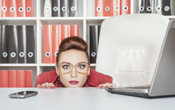 Business woman hiding behind table and afraid. Business woman with glasses hiding behind table and afraid Stock Photography