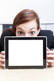 Business woman hiding behind tablet. Scared business woman hiding behind tablet pc in her office Royalty Free Stock Photo