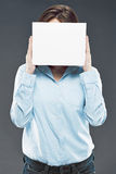 Business woman hiding face behind banner. Business woman hiding face behind white banner Royalty Free Stock Image