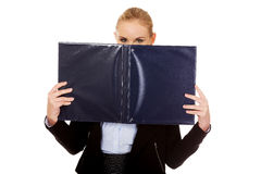 Business woman hiding face behind binder.  Stock Photography
