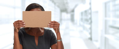 Business woman hiding face with cardboard. African american Business woman with card hiding her face Stock Photography