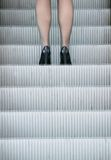 Business woman in high heels standing on escalator Stock Image