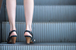 Business woman in high heels standing on escalators stairway.  Royalty Free Stock Photography