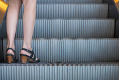 Business woman in high heels standing on escalators stairway.  Royalty Free Stock Images