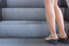 Business woman in high heels standing on escalators stairway.  Stock Photo