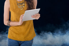 Business woman hold computer tablet with smoke in background. Business woman hold computer tablet with smokes in background Royalty Free Stock Photography