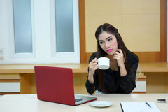 Business woman hold cup of coffee sitting at desk Stock Image