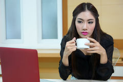 Business woman hold cup of coffee sitting at desk Stock Images