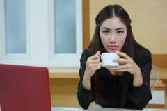 Business woman hold cup of coffee sitting at desk Stock Photo