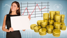 Business woman hold empty paper. Stacks of gold. Coins. Graphs and texts as backdrop Royalty Free Stock Photography