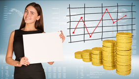 Business woman hold empty paper. Stacks of gold. Coins. Graphs and texts as backdrop Royalty Free Stock Photo