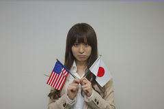 Business woman holding American and Japanese flags Royalty Free Stock Photography