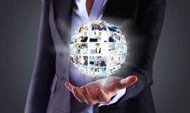 Business woman holding a ball of people Royalty Free Stock Photography