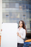 Business woman holding banner. Ad in her office Royalty Free Stock Photography