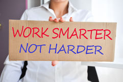 "Business woman holding a banner with ""Work smarter not harder"" Royalty Free Stock Image"