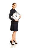 Business woman holding big clock. Stock Photo
