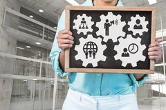 Business woman holding a blackboard with people in cogs graphics against office background. Digital composite of Business woman holding a blackboard with people Stock Photo