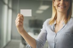 Business woman holding a blank business card. Stock Image
