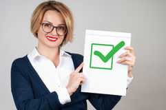 Business woman holding blank paper with check. Beautiful business woman holding blank paper with check mark or approved icon Royalty Free Stock Photo