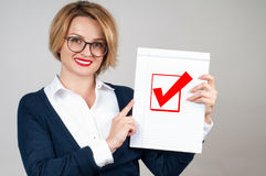 Business woman holding blank paper with check. Beautiful business woman holding blank paper with check mark or approved icon Stock Image