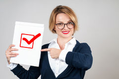 Business woman holding blank paper with check. Beautiful business woman holding blank paper with check mark or approved icon Stock Photography