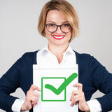 Business woman holding blank paper with check. Beautiful business woman holding blank paper with check mark or approved icon Stock Photos