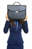 Business woman holding briefcase in front of face Stock Photo
