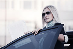 Fashion blond business woman in sunglasses by her car Royalty Free Stock Image