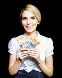 Business woman holding a cash bonanza. Attractive blonde business woman holding a cash bonanza of banknotes in her hand which she has won in an unexpected Royalty Free Stock Photography