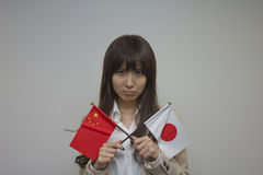 Business woman holding Chinese and Japanese flags Stock Photo