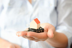 Business woman holding a cipher lock under a miniature house, symbolizing the concept of home security or insurance Stock Photos