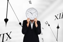 Business woman holding a clock against background with clocks. Digital composite of Business woman holding a clock against background with clocks Royalty Free Stock Photo
