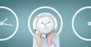 Business woman holding a clock against background with clocks Stock Photography