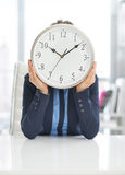 Business woman holding clock in front of face Stock Photos