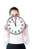 Business woman holding a clock in front of her face. Stock Photos