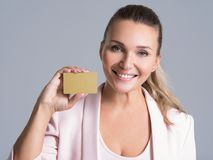 Business woman holding credit card against her face isolated. Studio portrait stock image