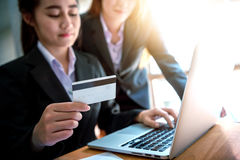 Business woman holding credit card on laptop for online shopping. Young business women holding credit card on laptop for online shopping Stock Images