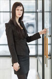 Business woman holding the door handle Stock Images