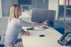 Business woman holding finger on touch screen. Woman working in office. Space for copy Stock Photography