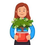 Business woman holding flower pot with money tree. Young business woman holding flower pot with money tree in her hands. Small business owner concept. Startup Royalty Free Stock Images