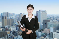 Business woman holding folder documents with city Stock Photo