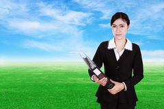 Business woman holding folder documents with green grass field Royalty Free Stock Image